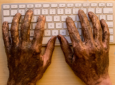 Hands dirty from working typing on keyboard